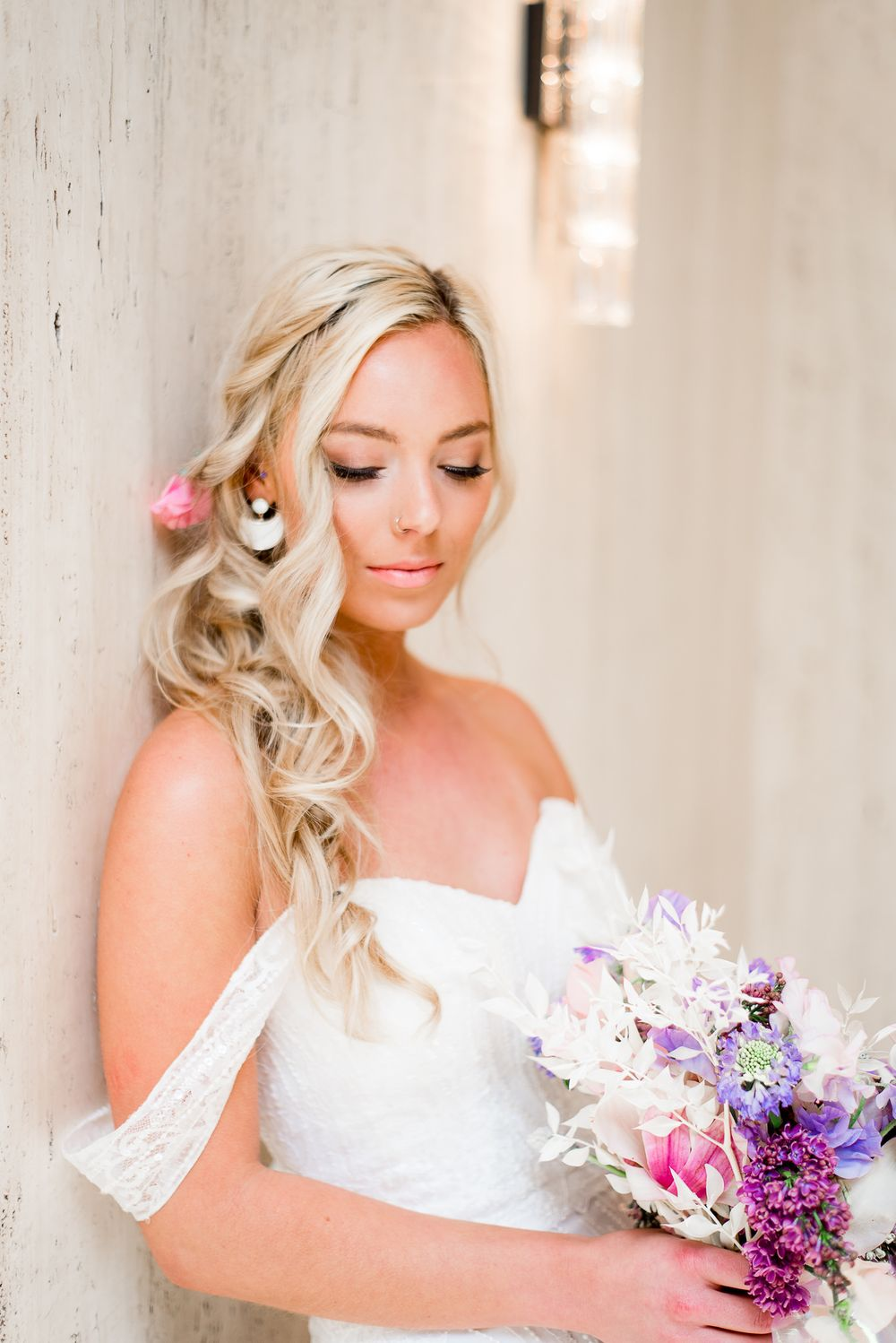 blonde bride with messy braid leaning on marble wall at pink purple white wedding bouquet
