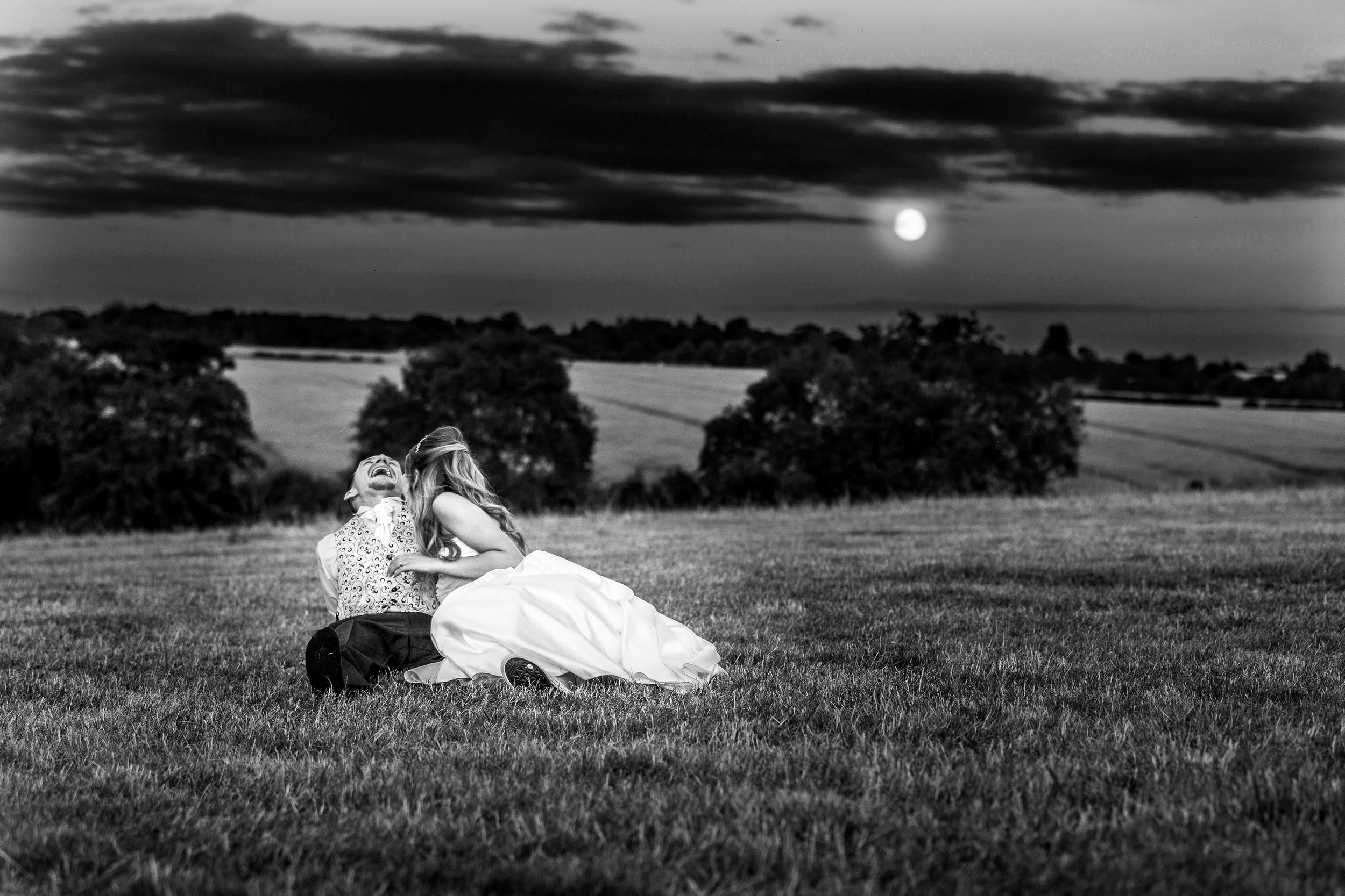 bride and groom sitting on the grass laughing