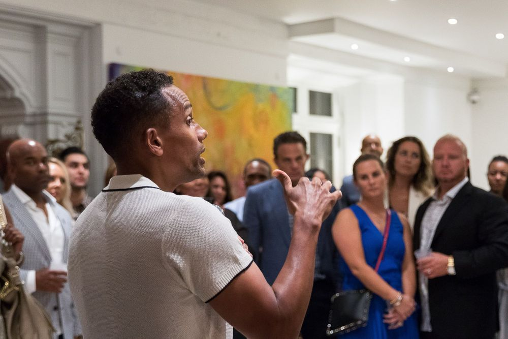 Hill Harper addressing a group of funders in his home during a fundraising event in Detroit.