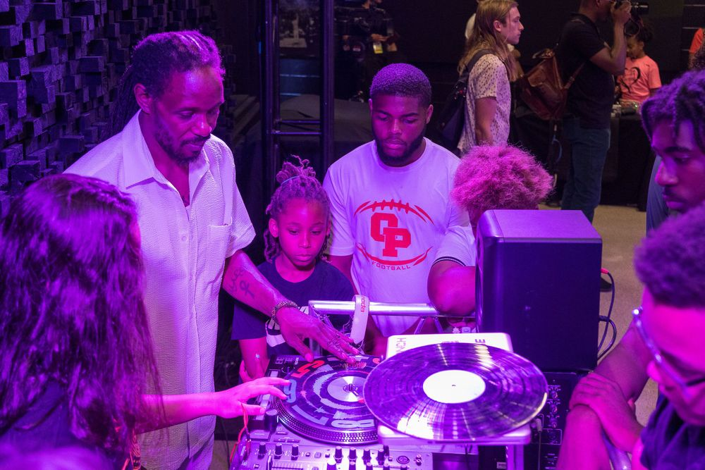 Image of a DJ teaching young kids about the music industry.