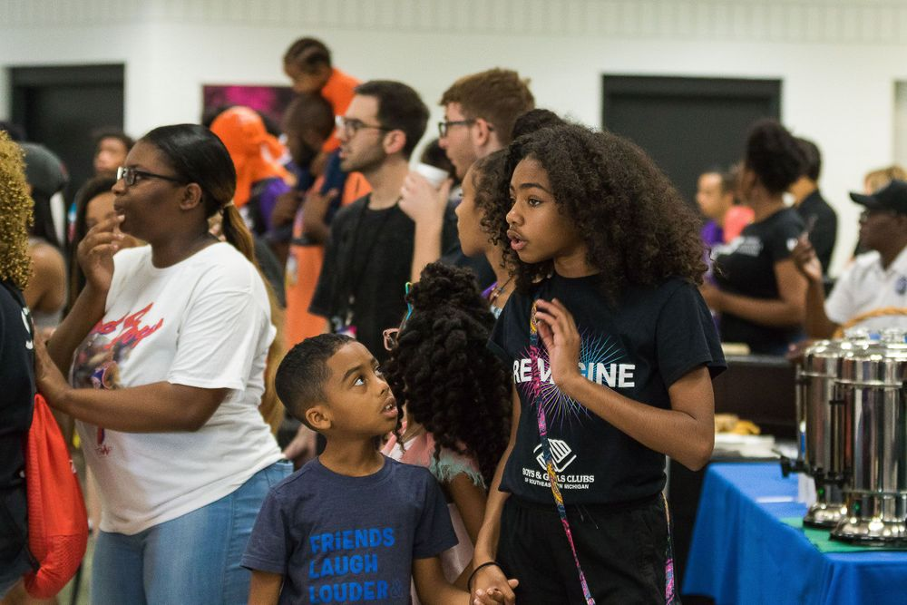 Image of a young black girl speaking to a younger black boy who is intently listening.