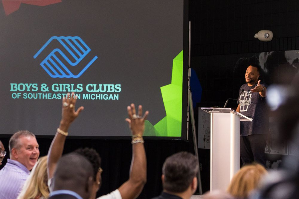 BGCSM CEO Shawn Wilson on stage pointing to Big Sean in a crowd with his arms raised.