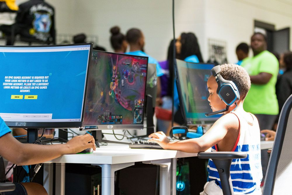 Young black boy intently learning on a large computer desktop.