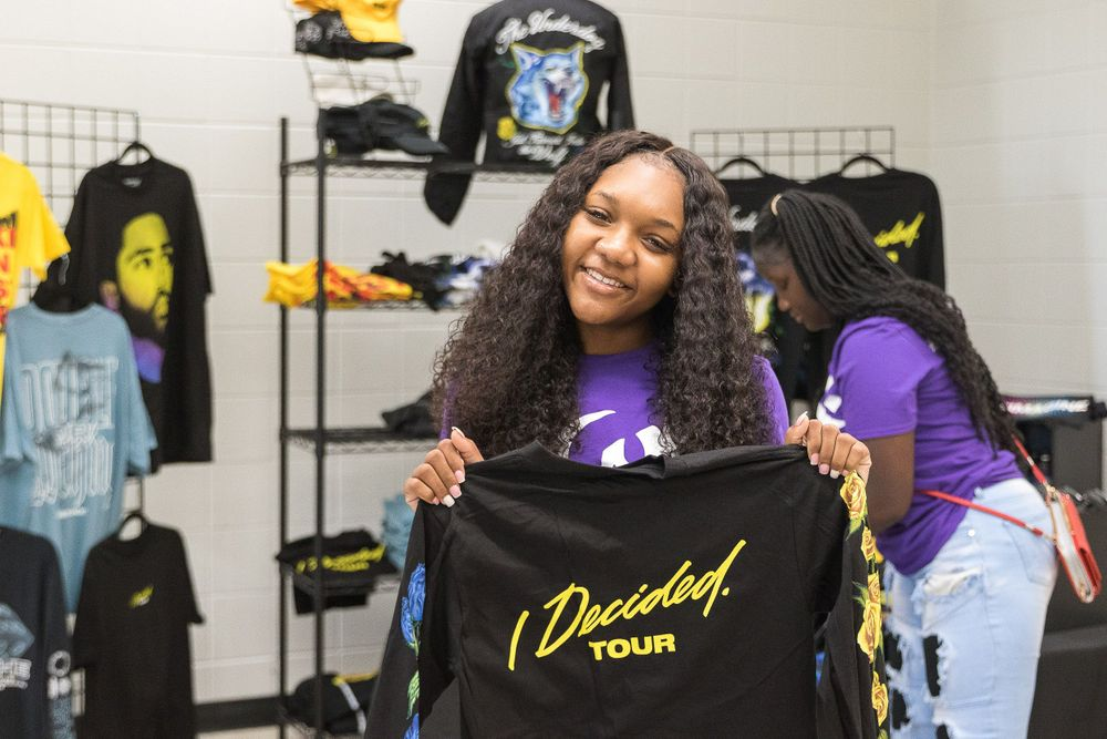 Black teenage girl smiling and holding an I Decided tour t-shirt
