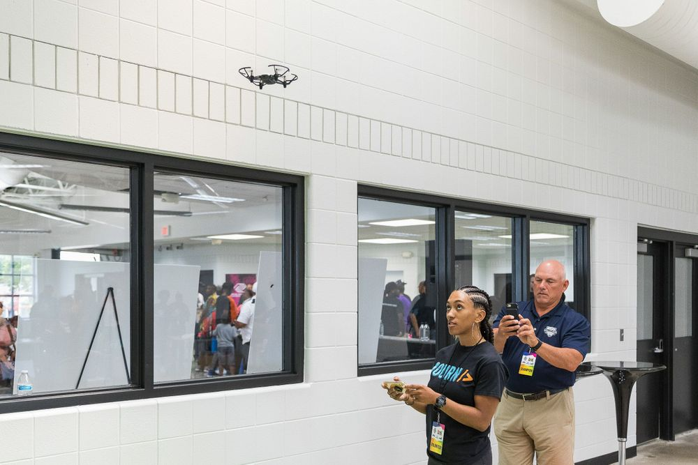 Black woman flying a drone above eye level inside an innovation space.