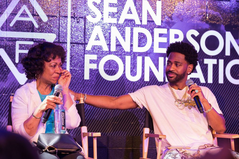Image of Big Sean compassionately comforting his mother on stage during an event.
