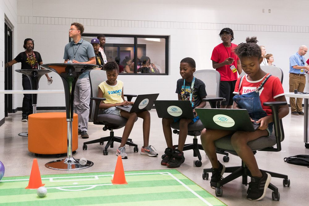 Image of young black students using computers to learn more about technology.