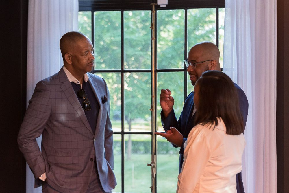 Image of a group of black professionals speaking in front of a light-filled window.