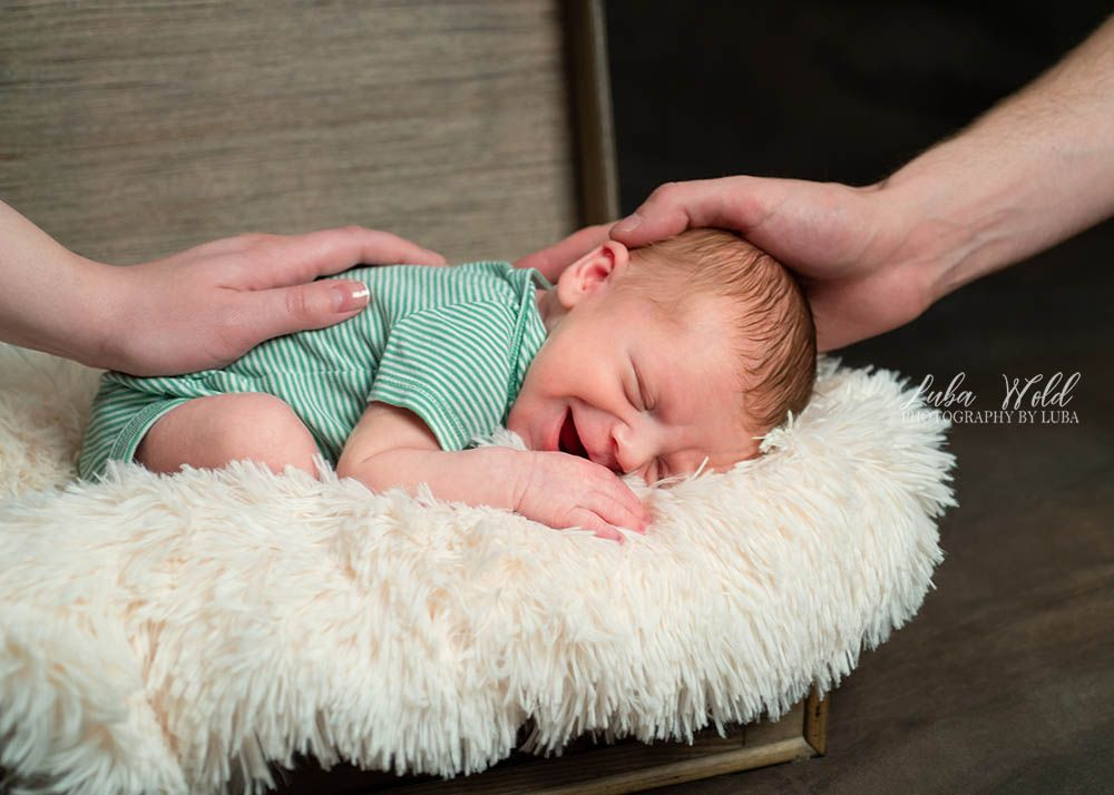 newborn family photographer luba wold spokane baby boy smiling parents hands