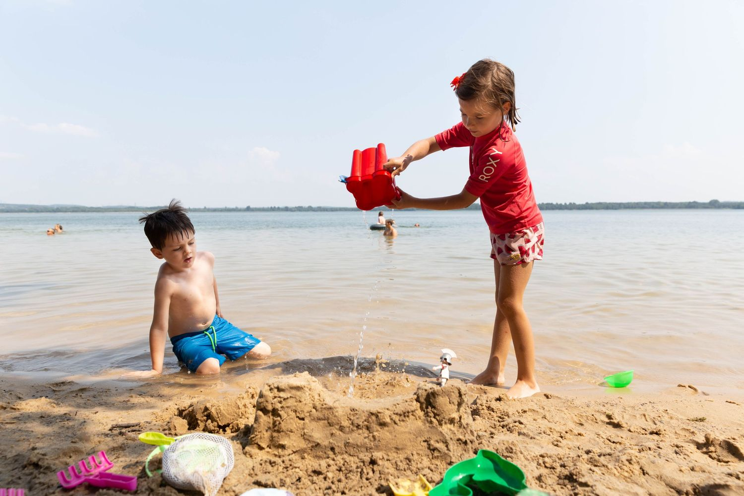boy and girl building sand castle