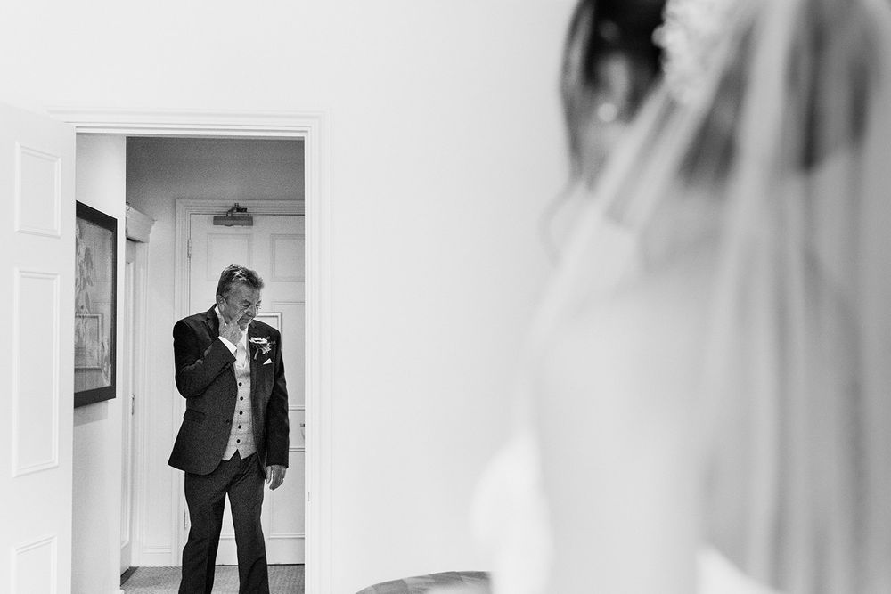 black and white photo of father seeing bride for first time