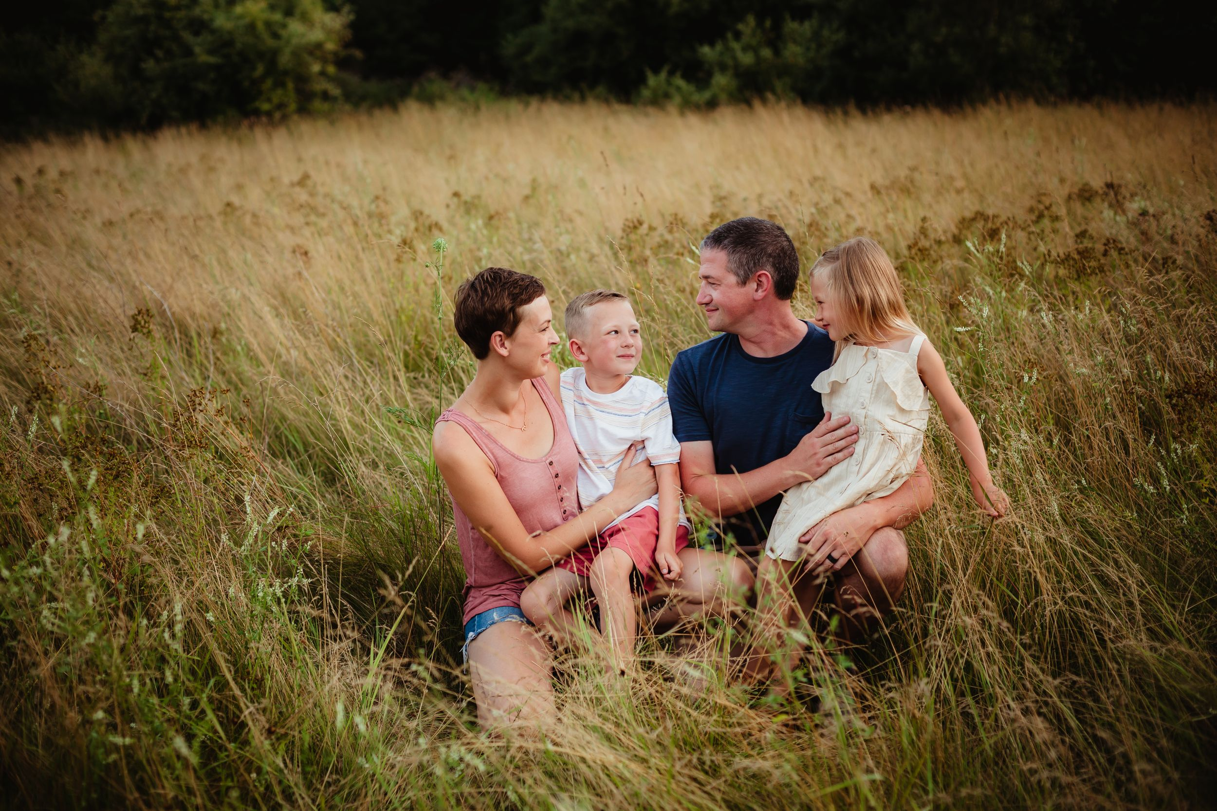 A mom, dad, brother, and sister sitting in a gold and green field. They are smiling at each other.