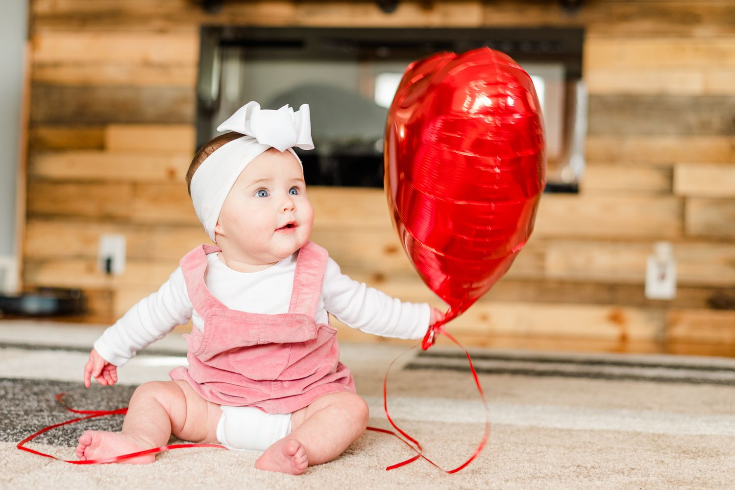 Lifestyle family photoshoot in the home with 6 month old baby holding a heart balloon in Gibsonia, Pennsylvania