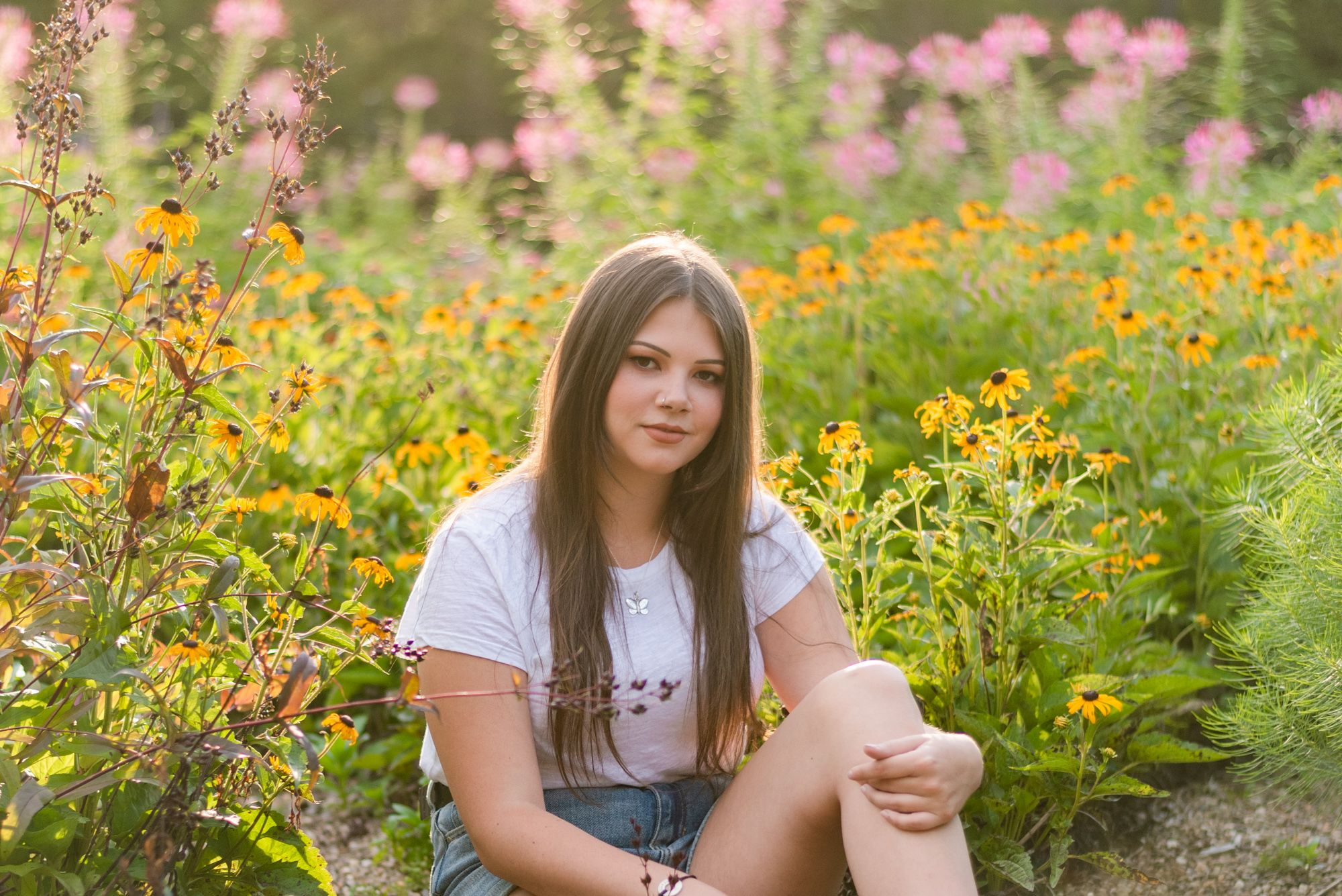 Girl sitting in flowers in golden sunlight at Hartwood Acres in Pittsburgh Pennsylvania