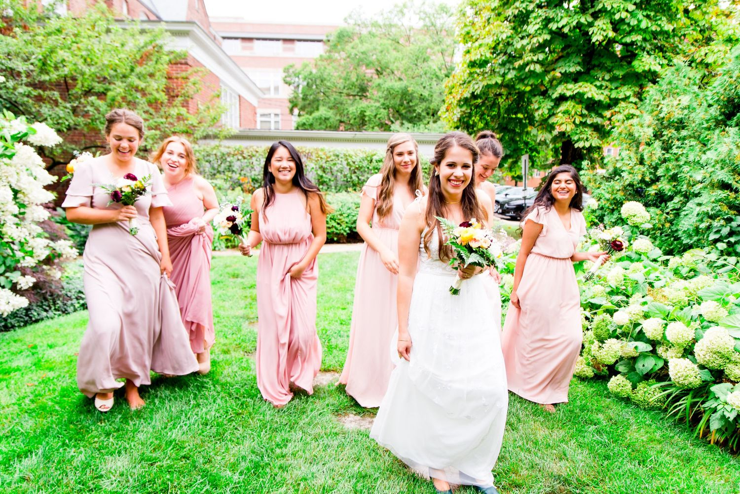 bride and bridesmaids in blush dresses walking through the Woman's Club of Evanston garden in the summer