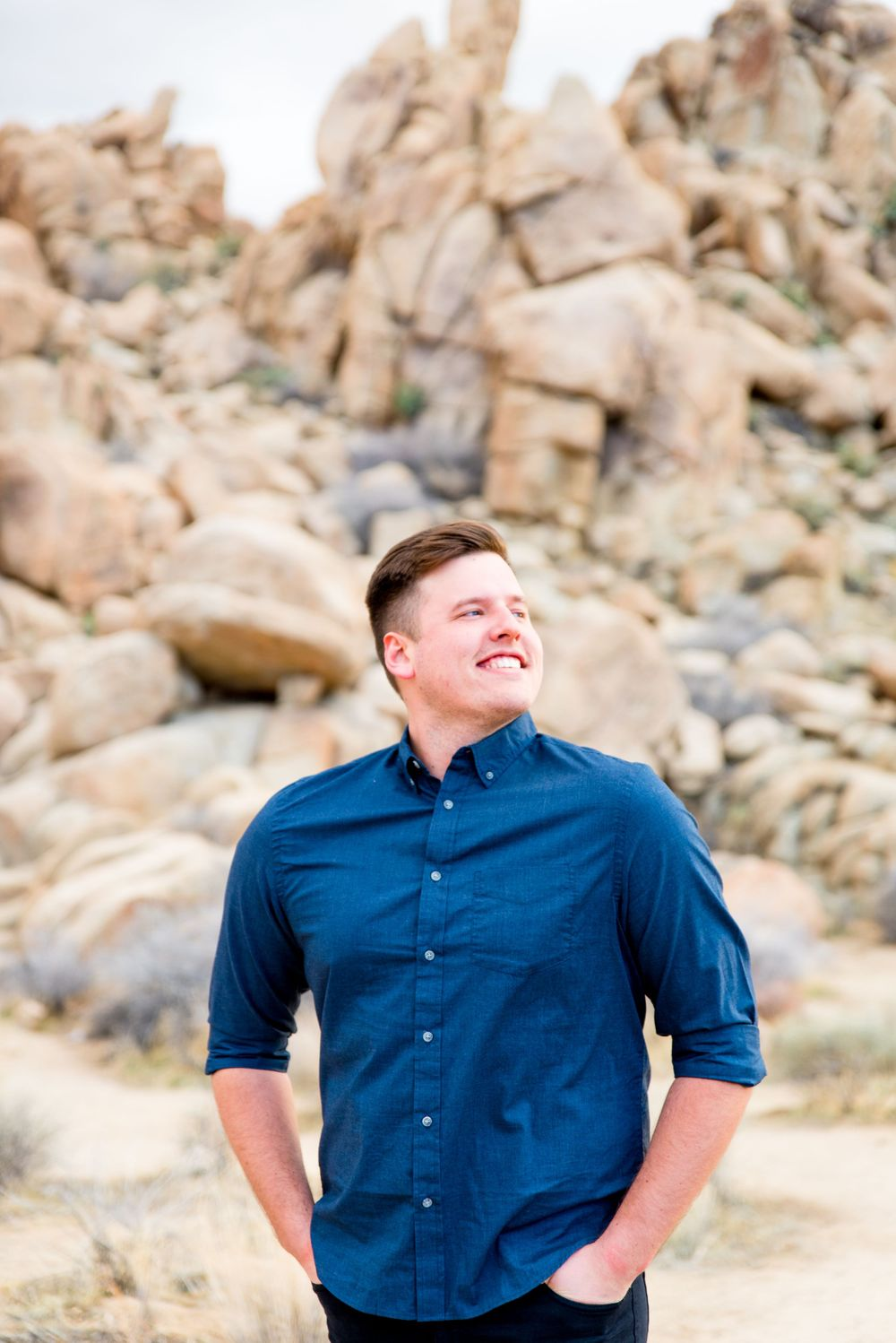 man in blue button down shirt looks to the right and smiles in front of rocks at Joshua Tree National Park