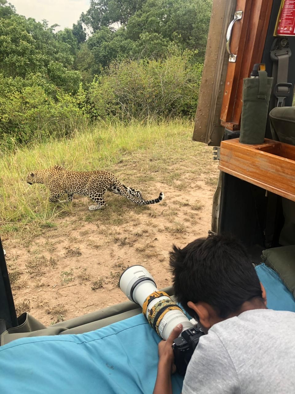 a young photographer getting very close to a leopard in Masai Mara