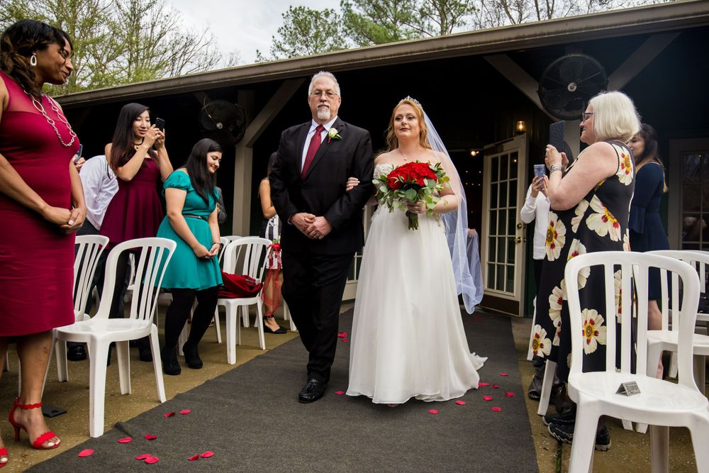 Father walks his daughter the bride down the aisle during a wedding ceremony at Winter Green Woods in Lexington, SC