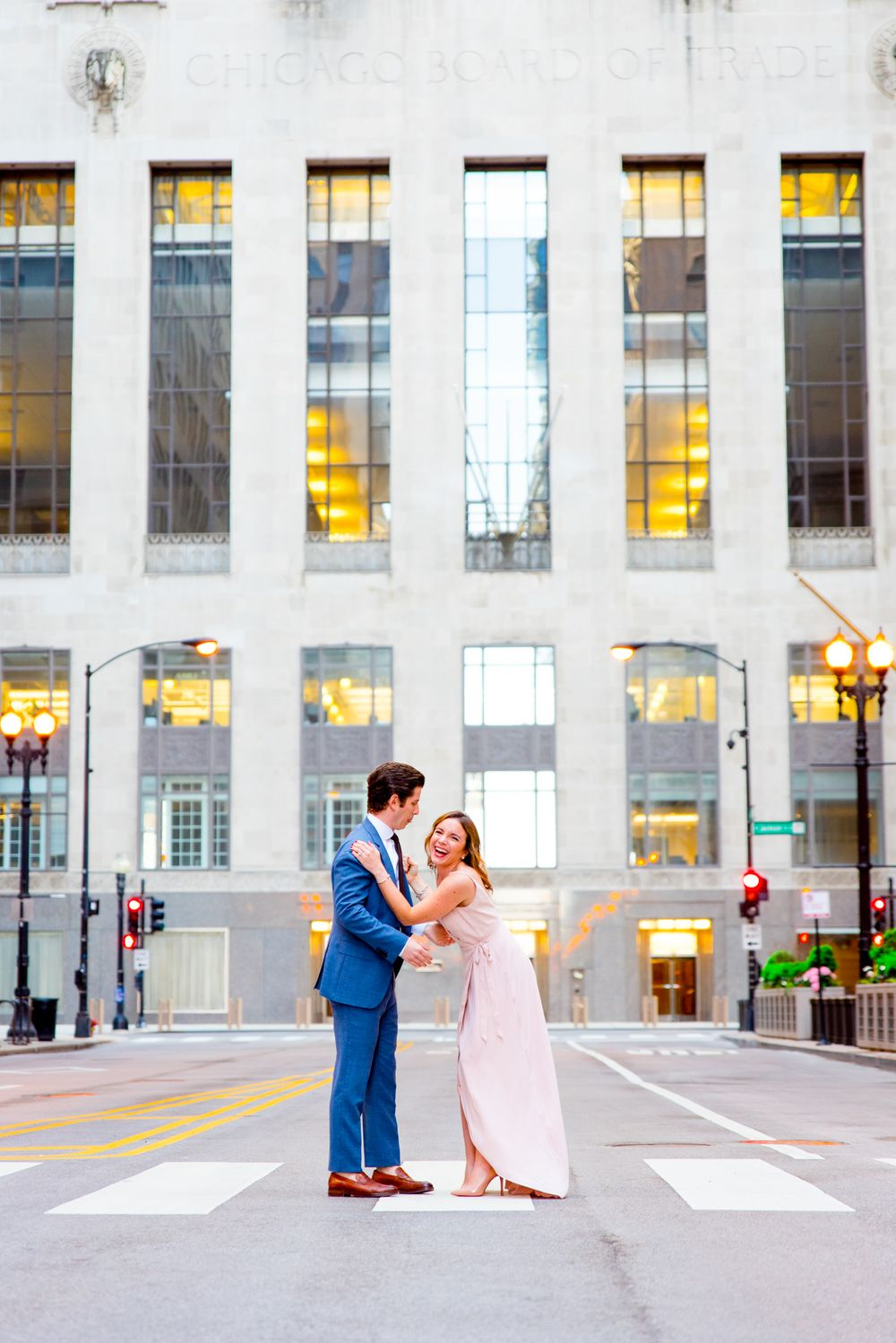 young couple laughs in front of Chicago Board of Trade for sunset engagement pictures in Chicago