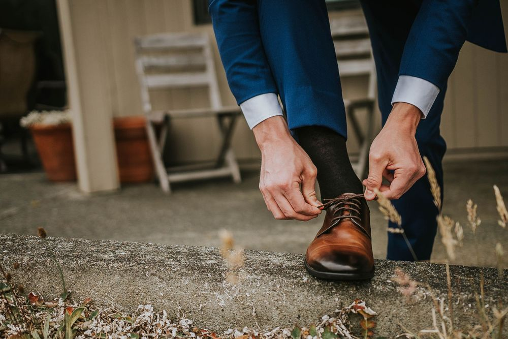 rebecca skidgel photography groom tying shoes getting ready