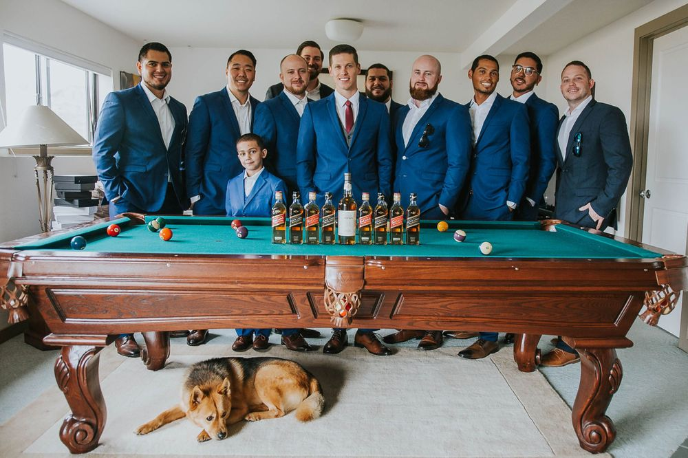 rebecca skidgel photography groom and groomsmen around pool table with whiskey