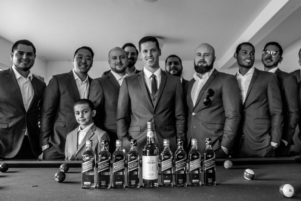 rebecca skidgel photography whiskey on pool table with groomsmen in the background