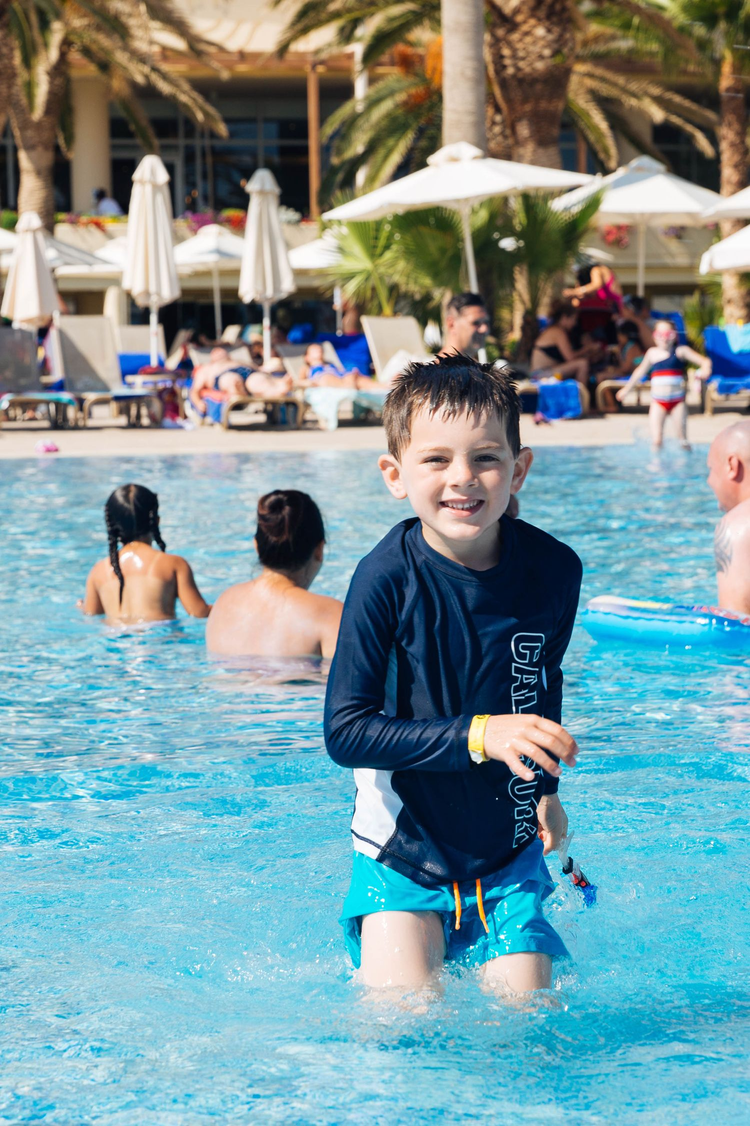 boy in swimming t-shirt in a pool smiling