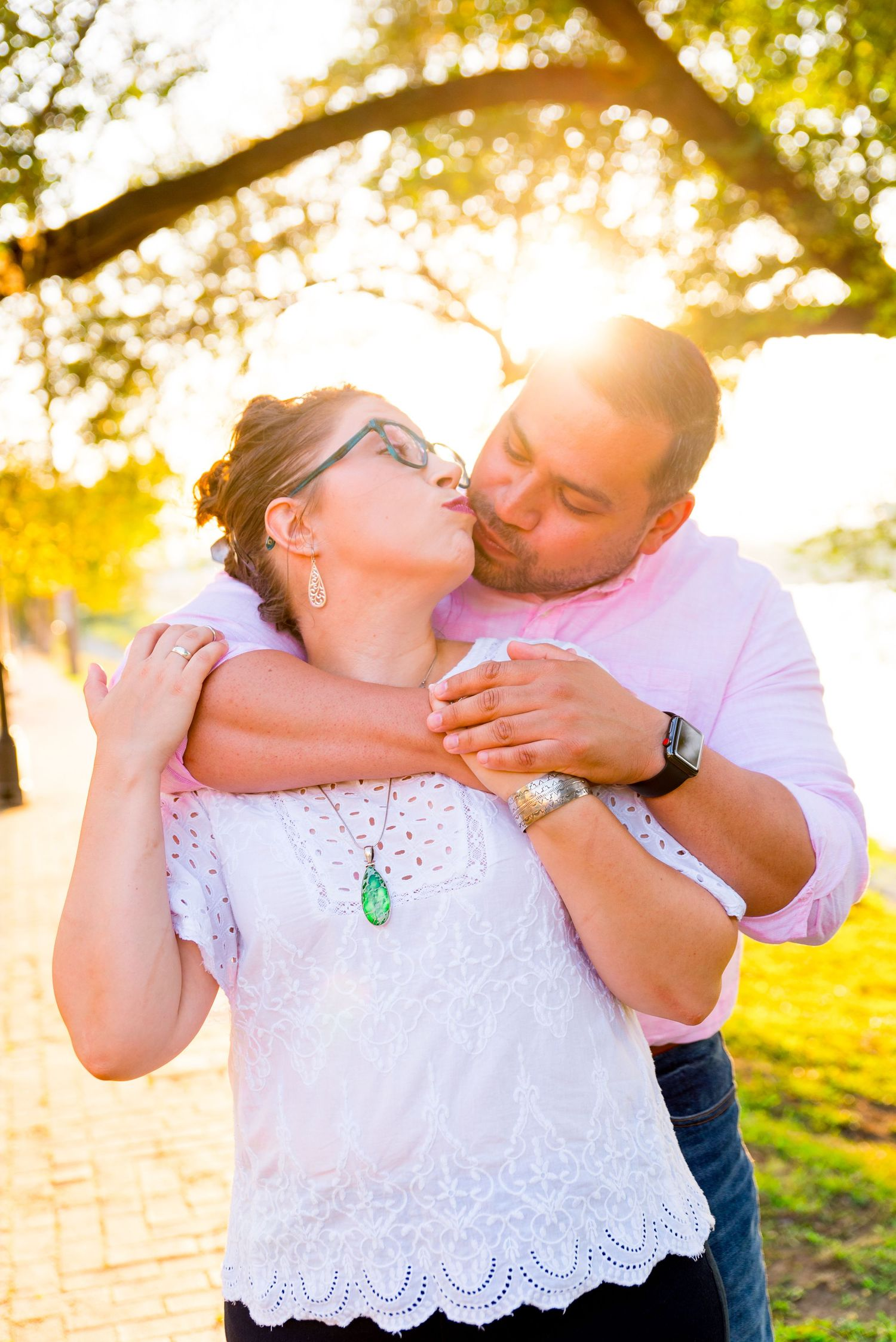 man in pink shirt hugs his fiancee in white shirt from behind and they kiss