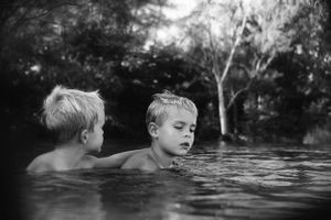 Black and white sibling photo of boys playing at Ft. Desoto