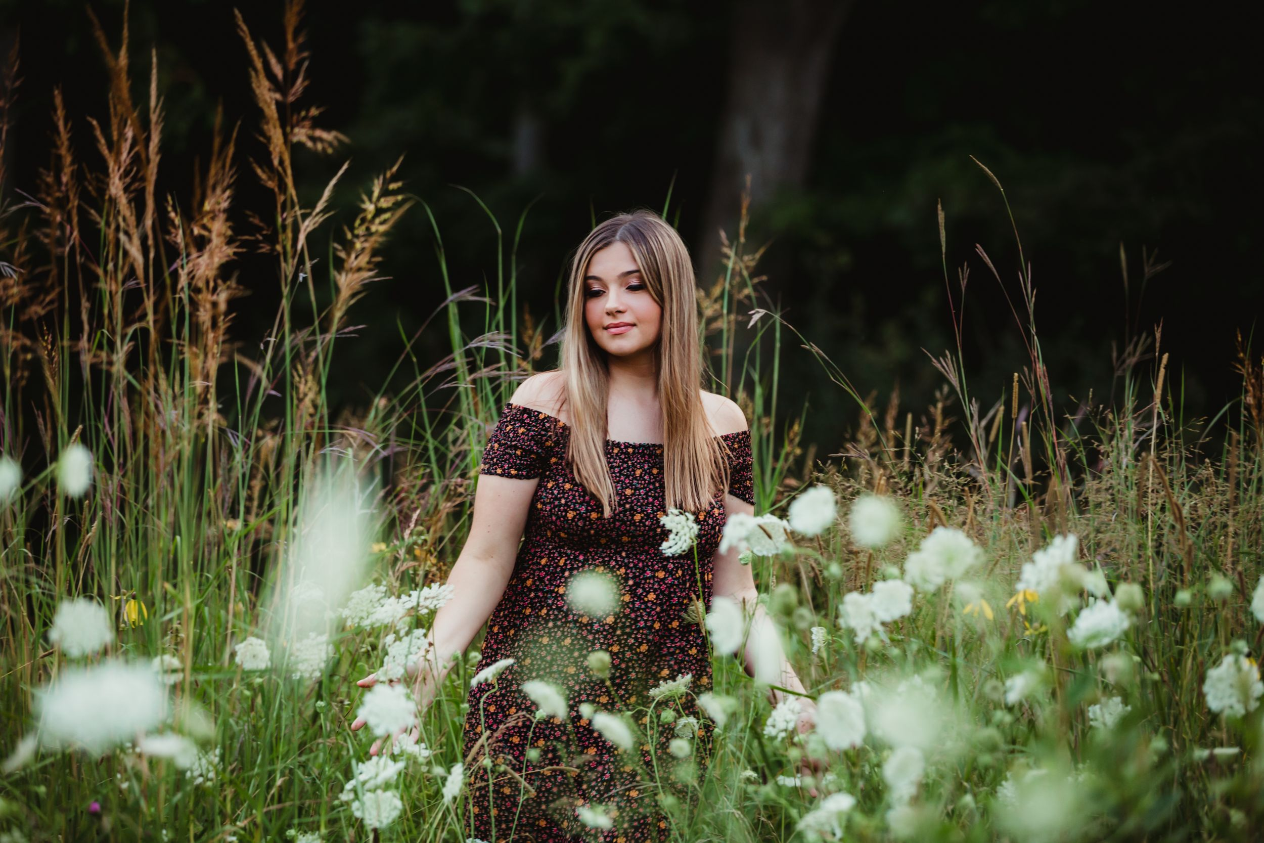 High school senior girl walking through a field of long grass and flowers. She is wearing a dark dress with tiny flowers