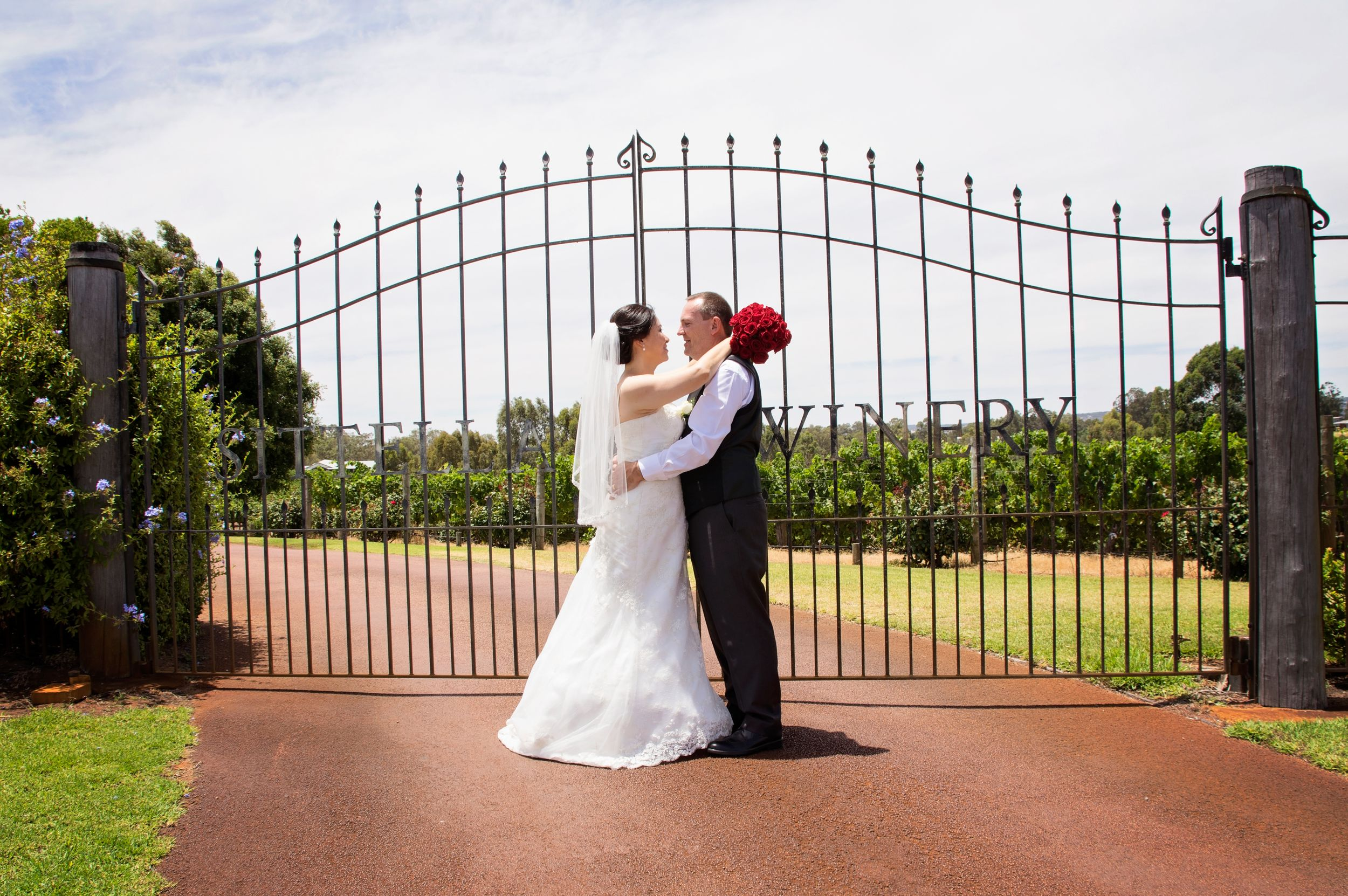 bride and groom posing infront of sitella winery gate