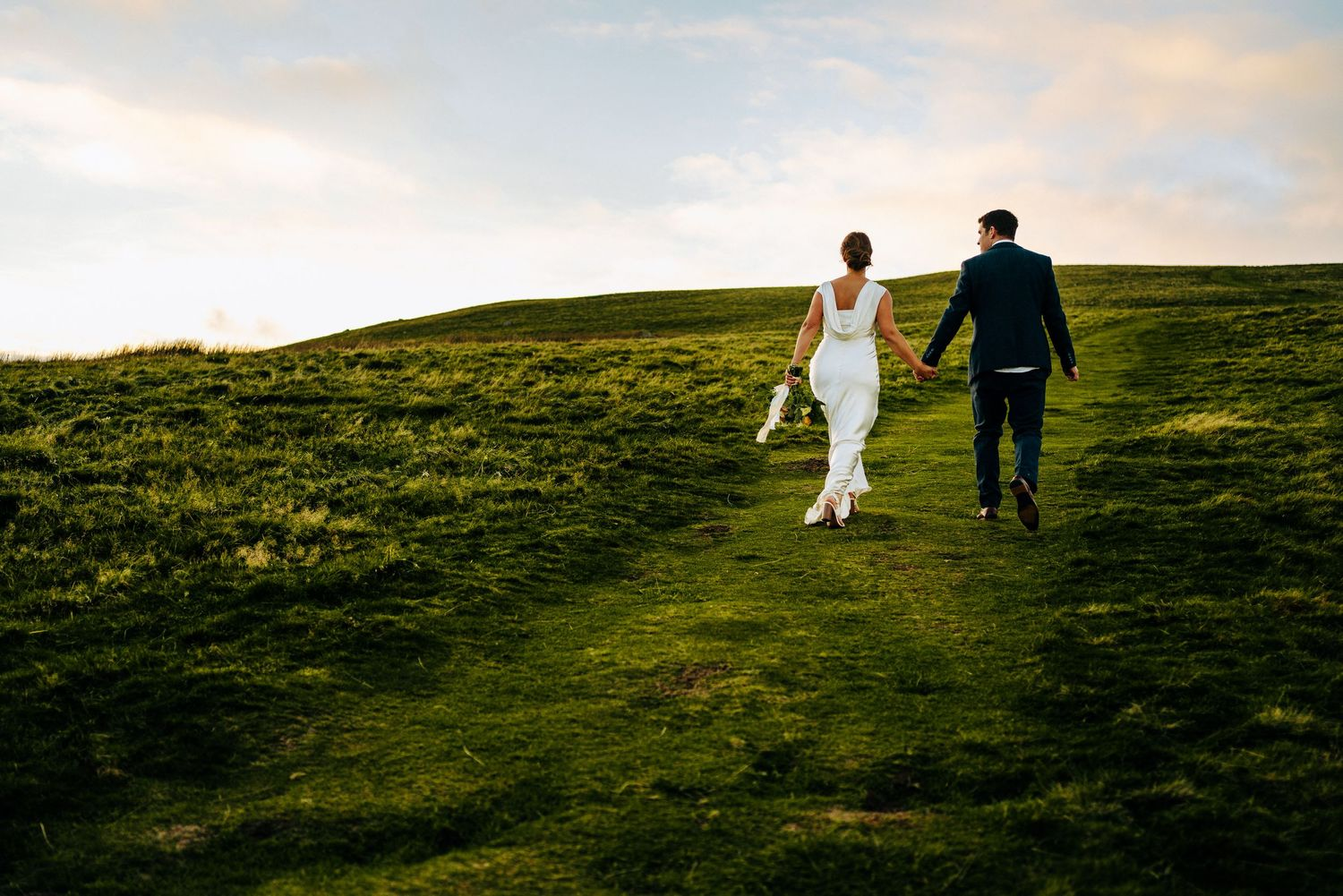 Lake District Wedding Photography - Bride and Groom walking up a fell