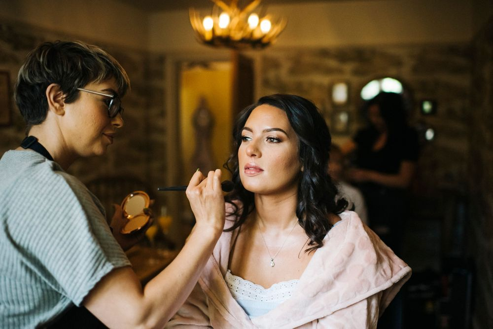 bridesmaid having her makeup done in the lodge at eaves hall, Ribble Valley wedding photographer