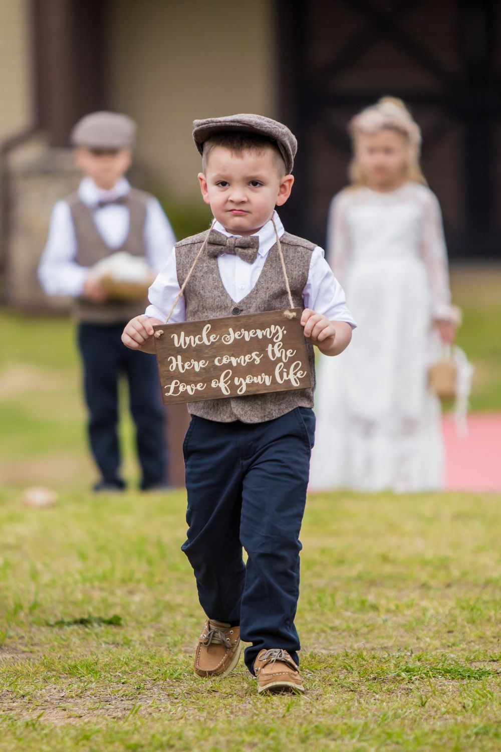 Ring bearer holds a sign during a wedding ceremony at the Farm at Ridgeway in Ridgeway, SC