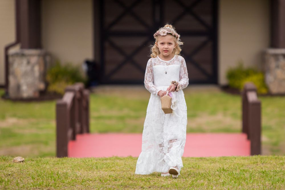 Flower girl walks down the aisle during a wedding ceremony at the Farm at Ridgeway in Ridgeway, SC