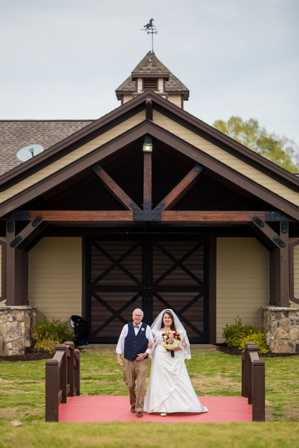 The father walks the bride across the bridge during a wedding ceremony at the Farm at Ridgeway in Ridgeway, SC