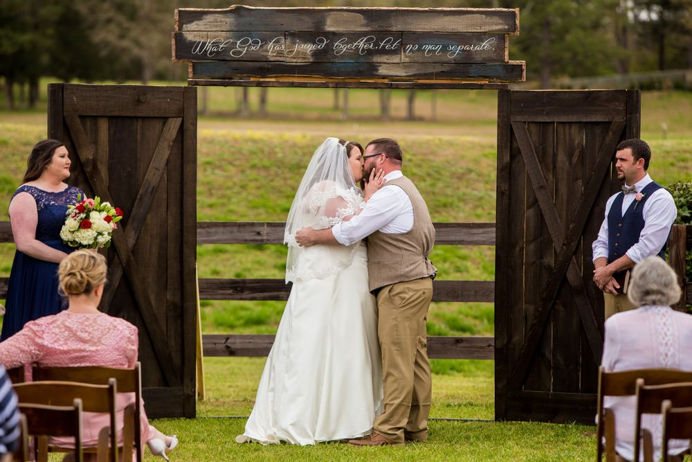 Bride and groom share their first kiss during a wedding ceremony at the Farm at Ridgeway in Ridgeway, SC