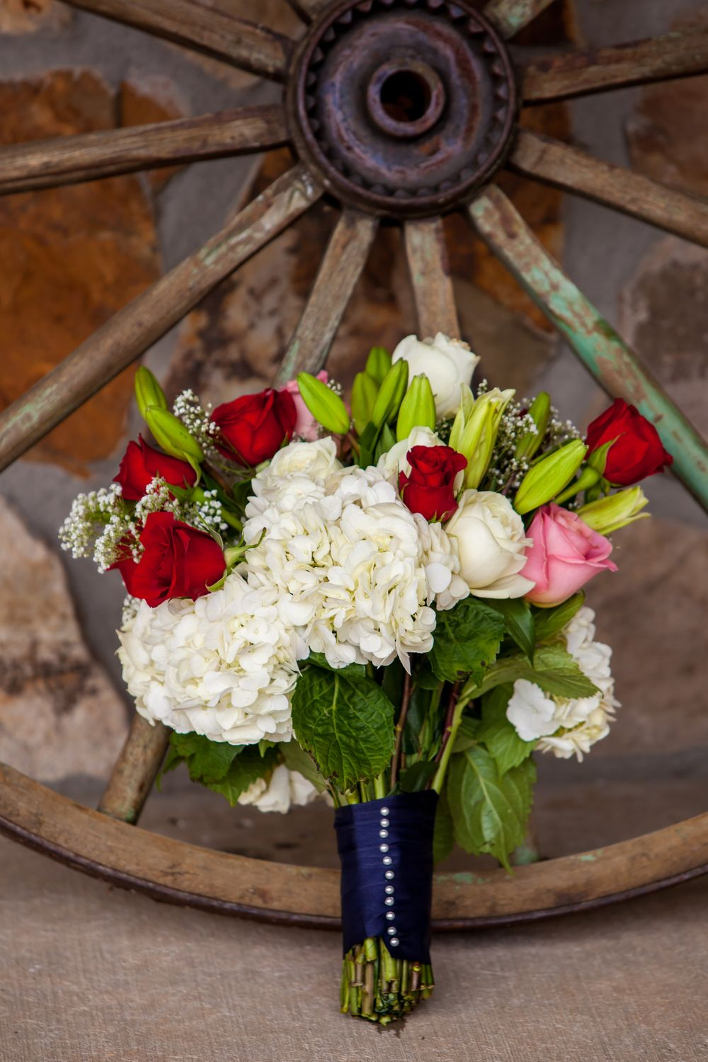 A bridal bouquet in front of a rusty wagon wheel at the Farm at Ridgeway in Ridgeway, SC