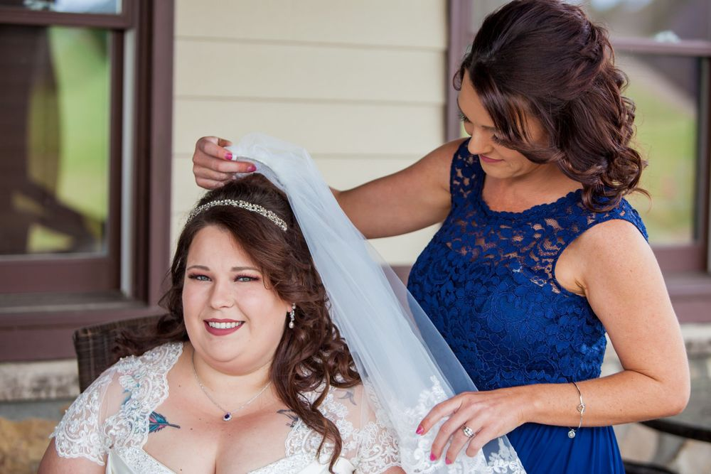 Bridesmaid puts the veil on the bride before a wedding at the Farm at Ridgeway in Ridgeway, SC