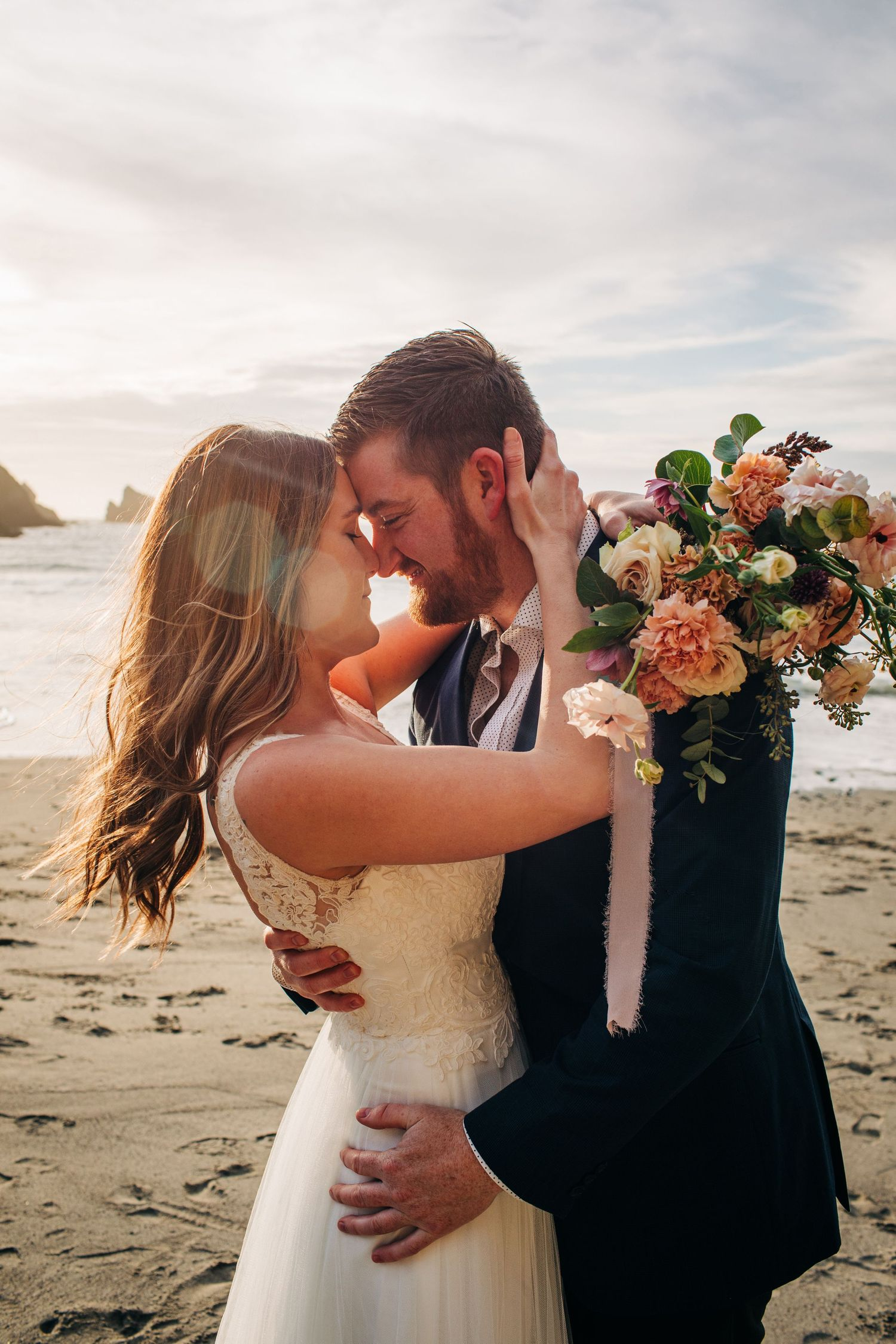 A newly married couple embraces on their elopement wedding day in Mendocino, California.