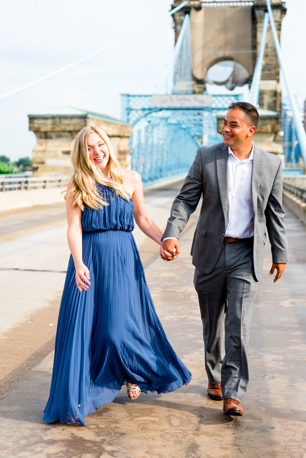 man in grey suit holds hand of blonde woman in blue dress as they walk near the Roebling Bridge for engagement pictures