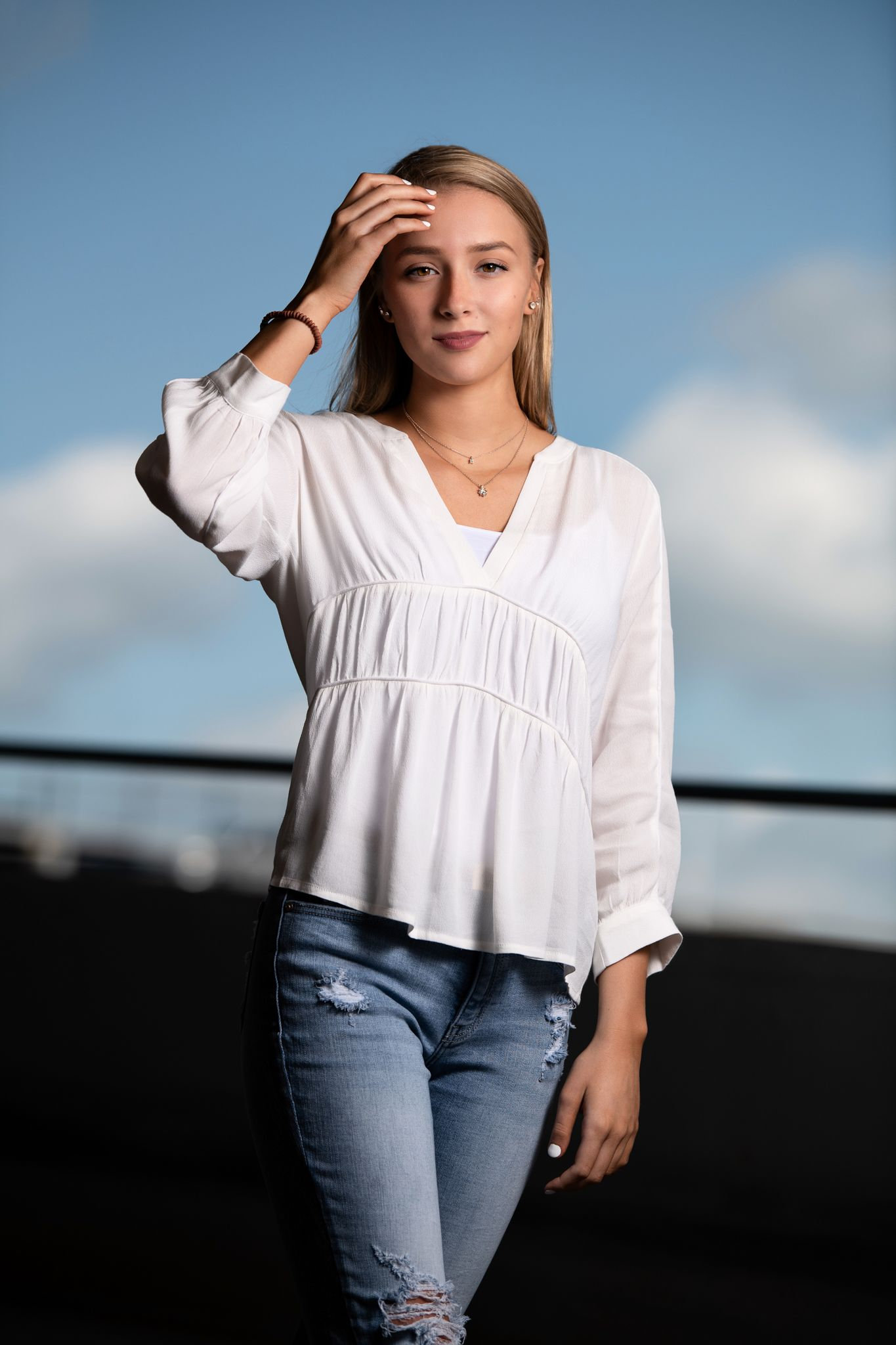 Senior session with a girl in white top and torn blue jeans atop a parking garage, urban setting