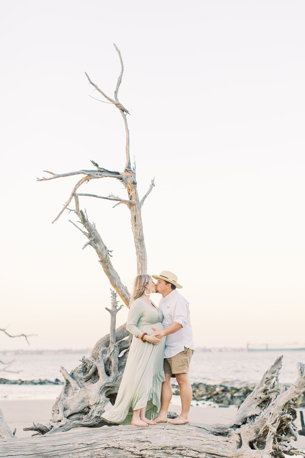 kayley and josh taking their maternity session photos at driftwood beach on jekyll island, ga