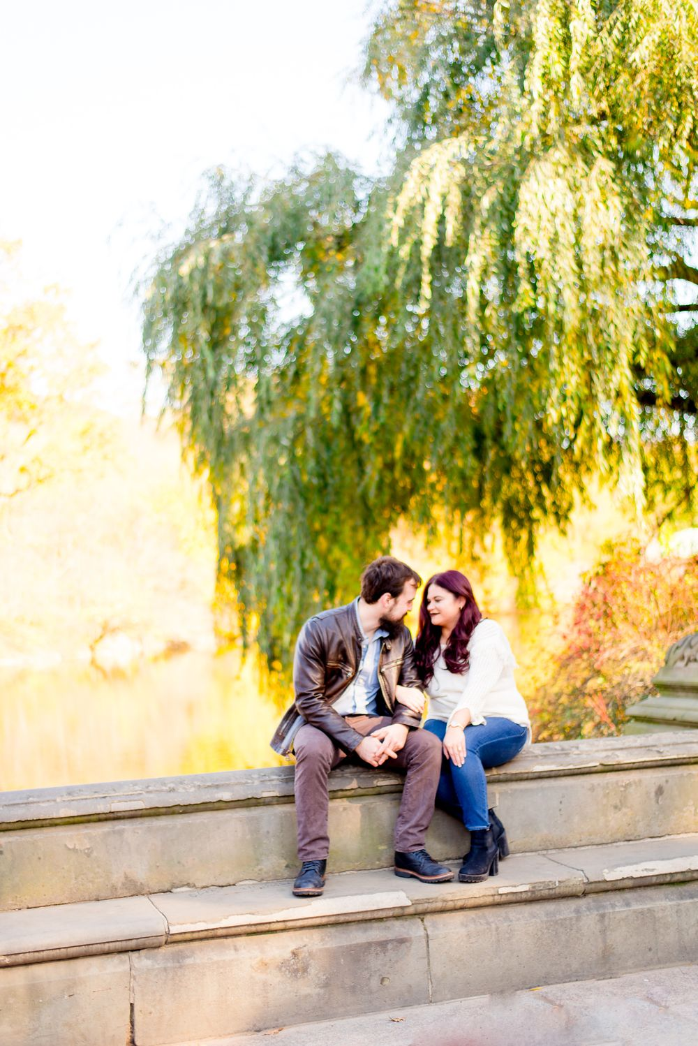 engaged man and woman sitting by the pond at Central Park for fall engagement pictures