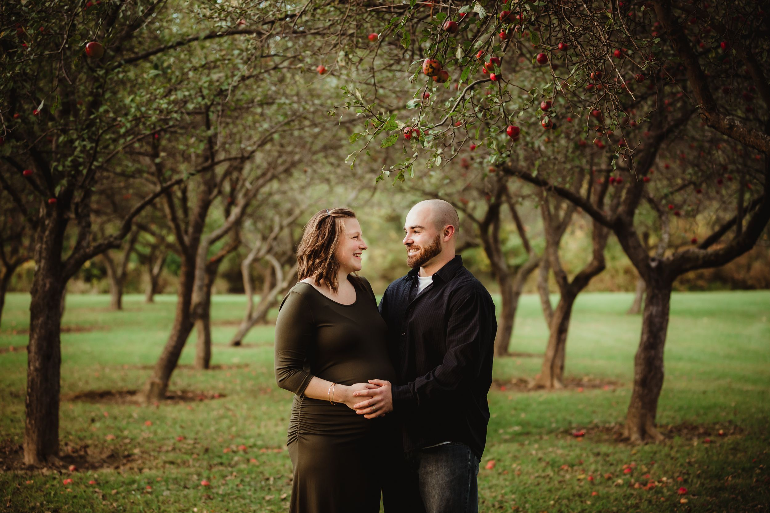 Pregnant woman and her husband smiling at each other standing between rows of apple trees.