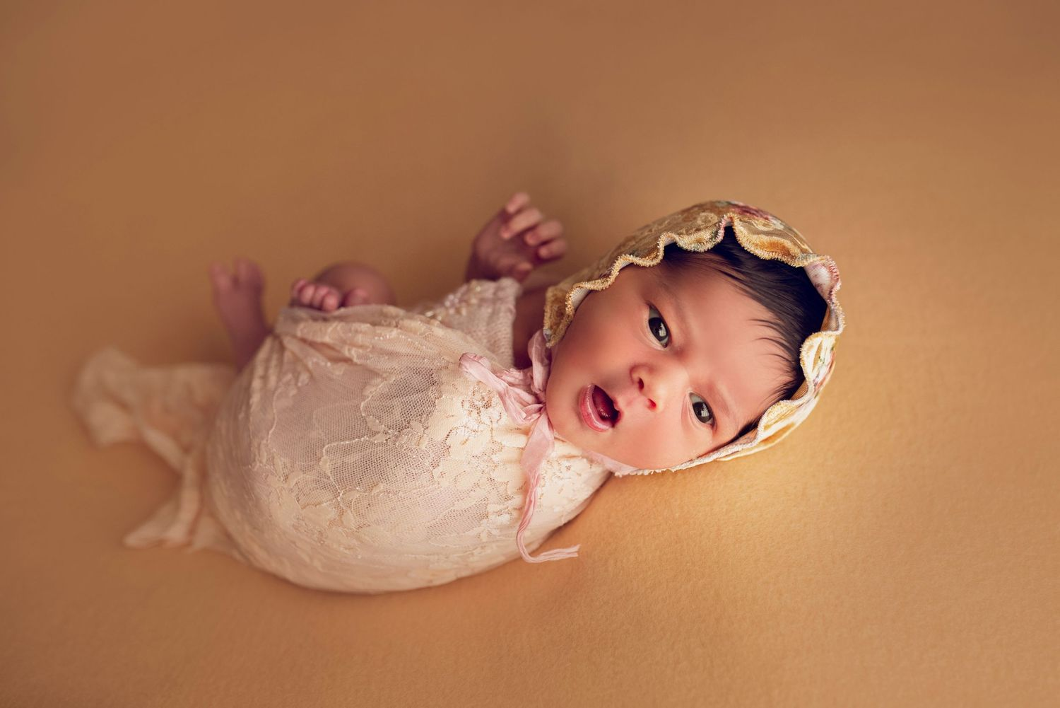 newborn baby girl wrapped in lace peach bonnet