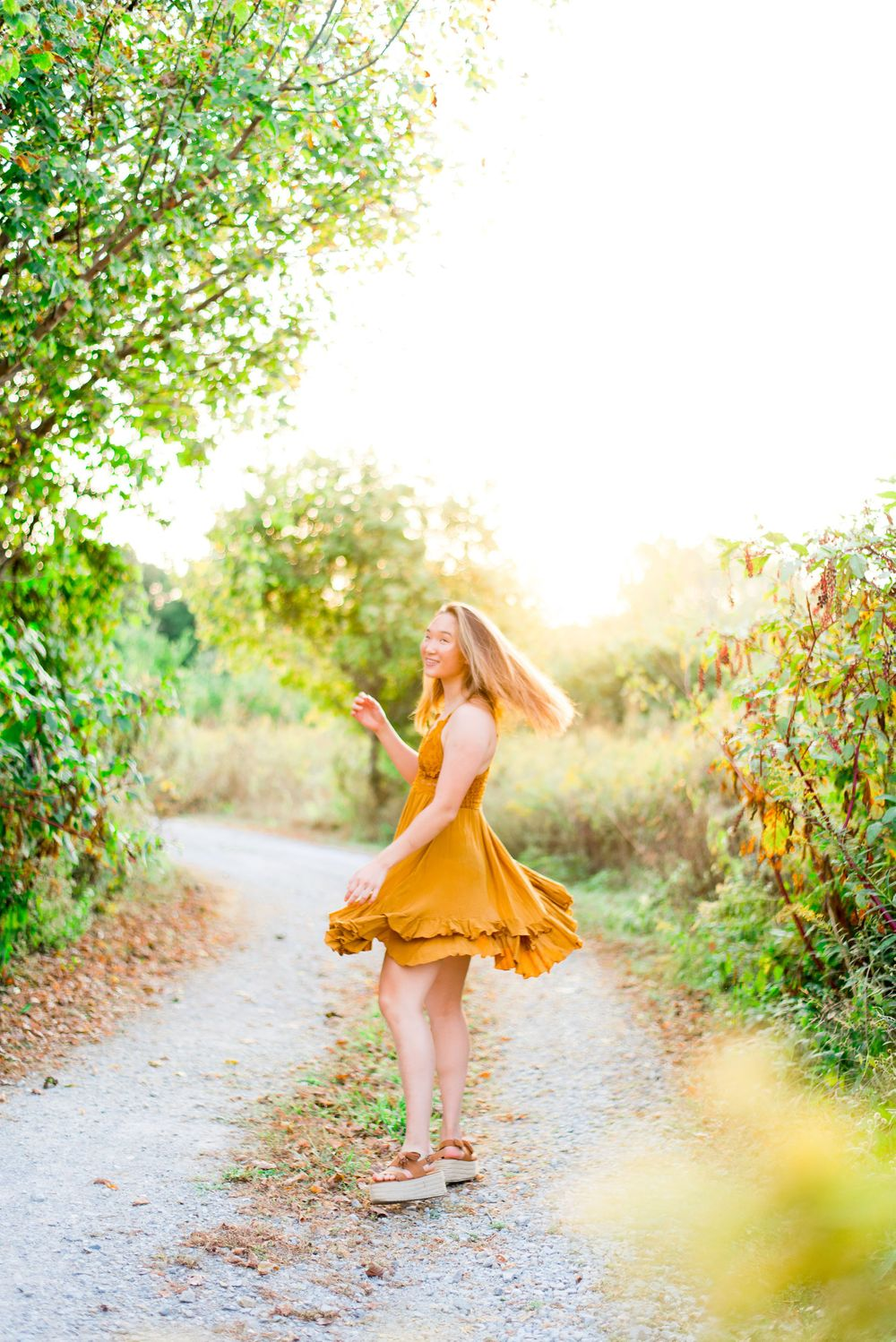 young woman in yellow Adella dress spinning around on a gravel path