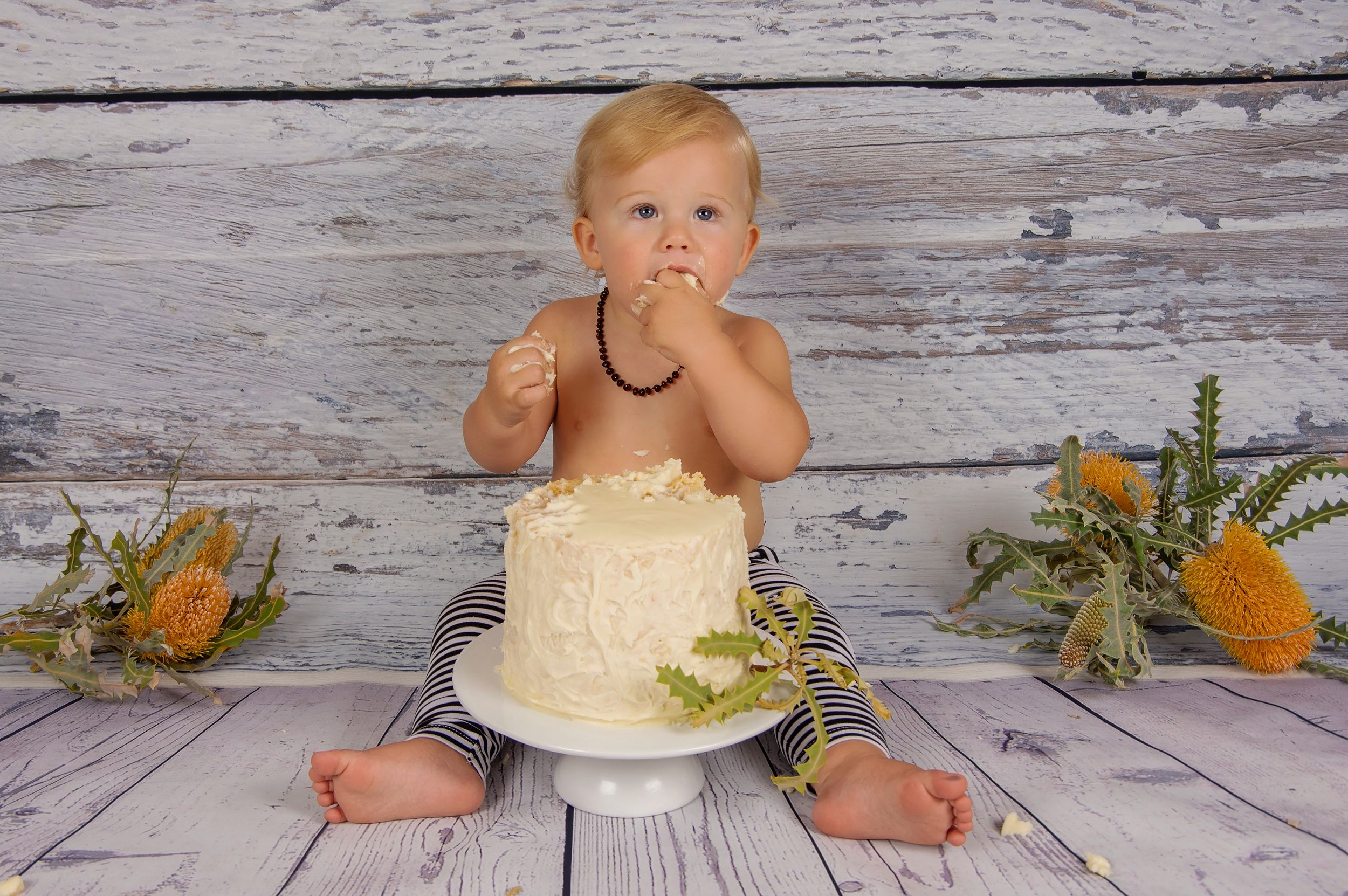 blonde baby eating cake on grey backdrop