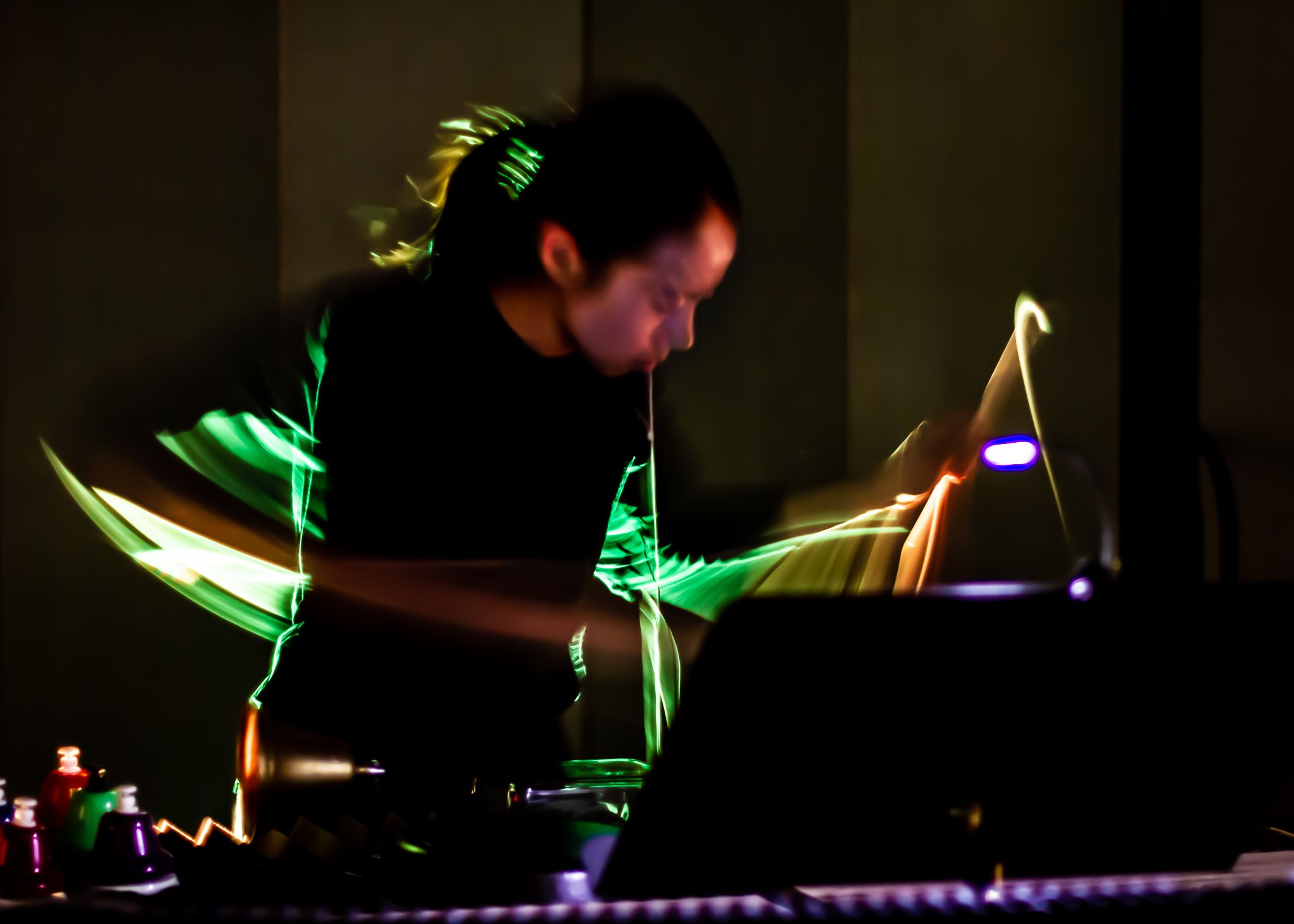 Percussionist Rebekah Ko is surrounded by swoops of light in an otherwise dark room.