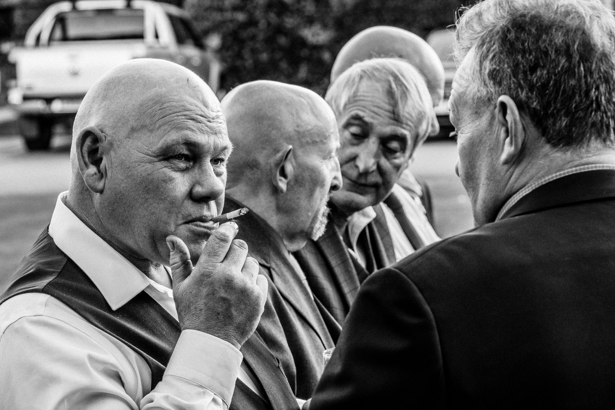 Black and white image of male guests during wedding reception in Yorkshire